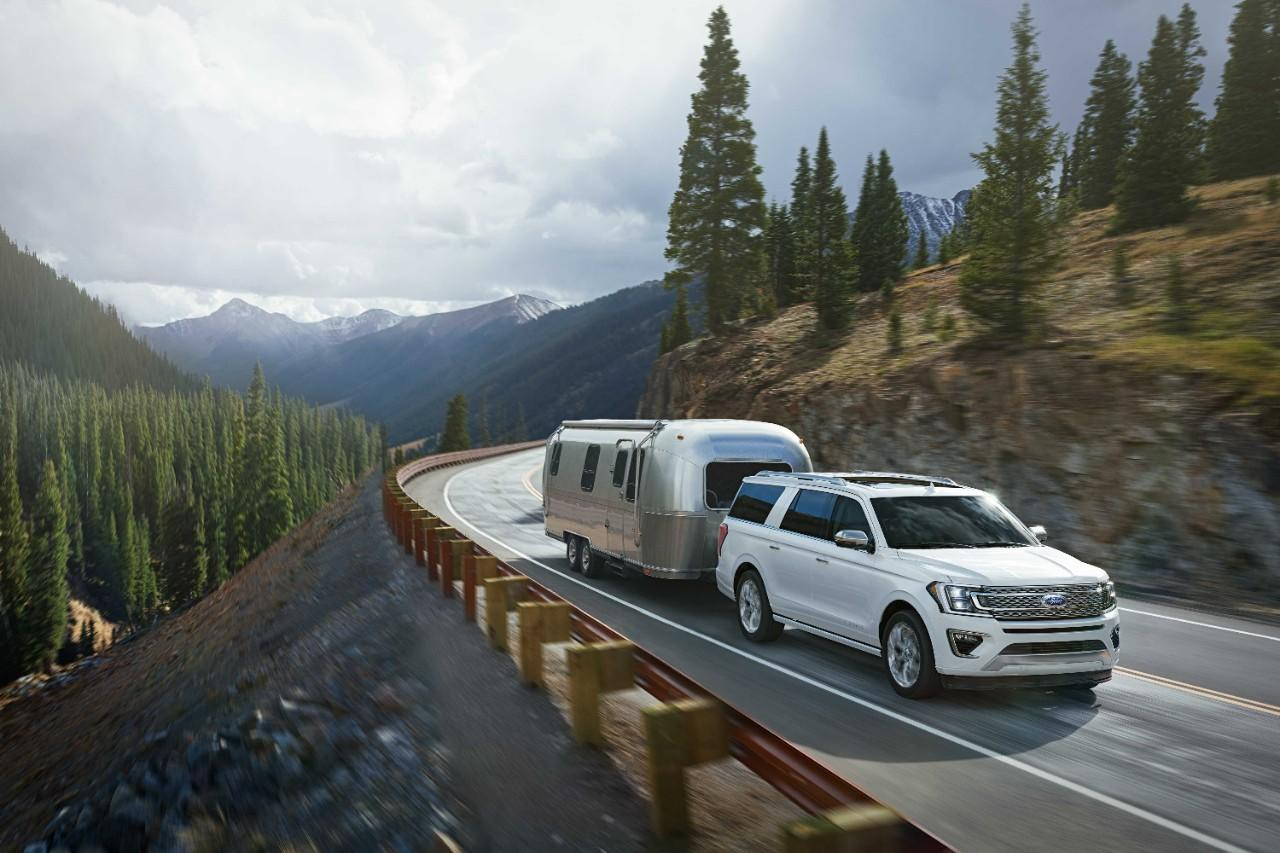 Ford Expedition blanche tirant une caravane sur route montagneuse