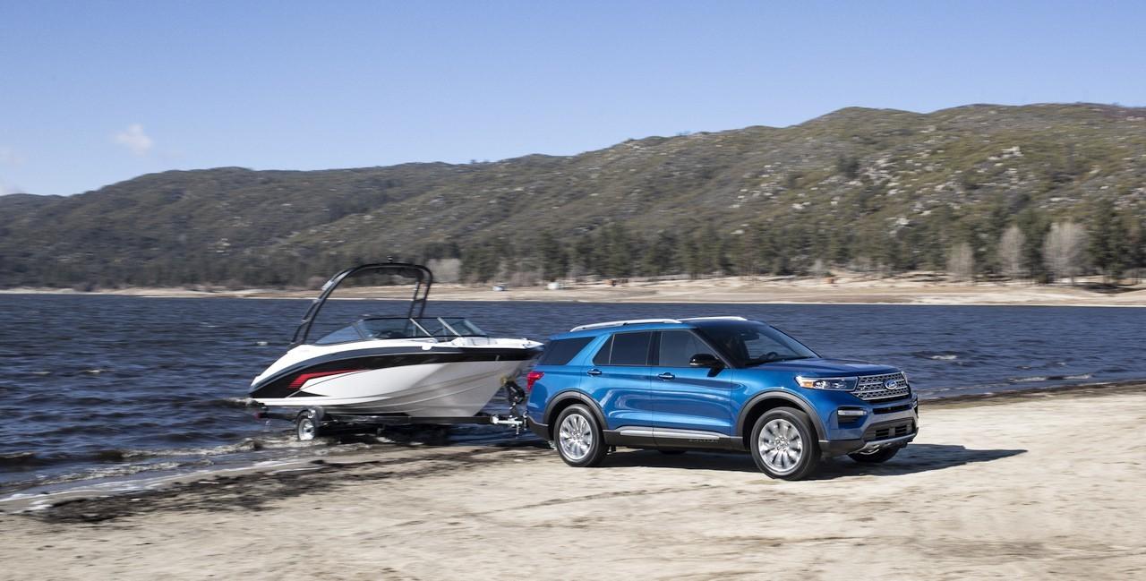 Ford Explorer hybride bleu métallique remorquant un yacht