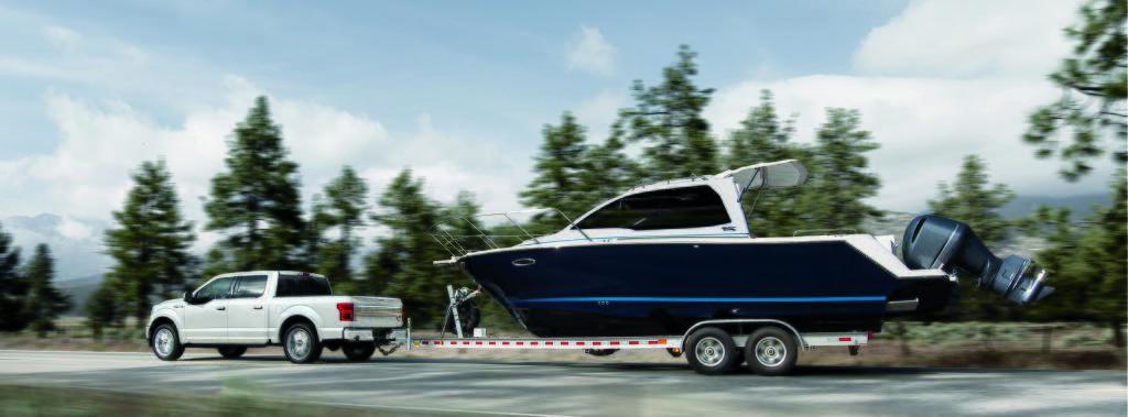 Ford F-150 LTD blanc tirant un yacht 2 fois sa grosseur