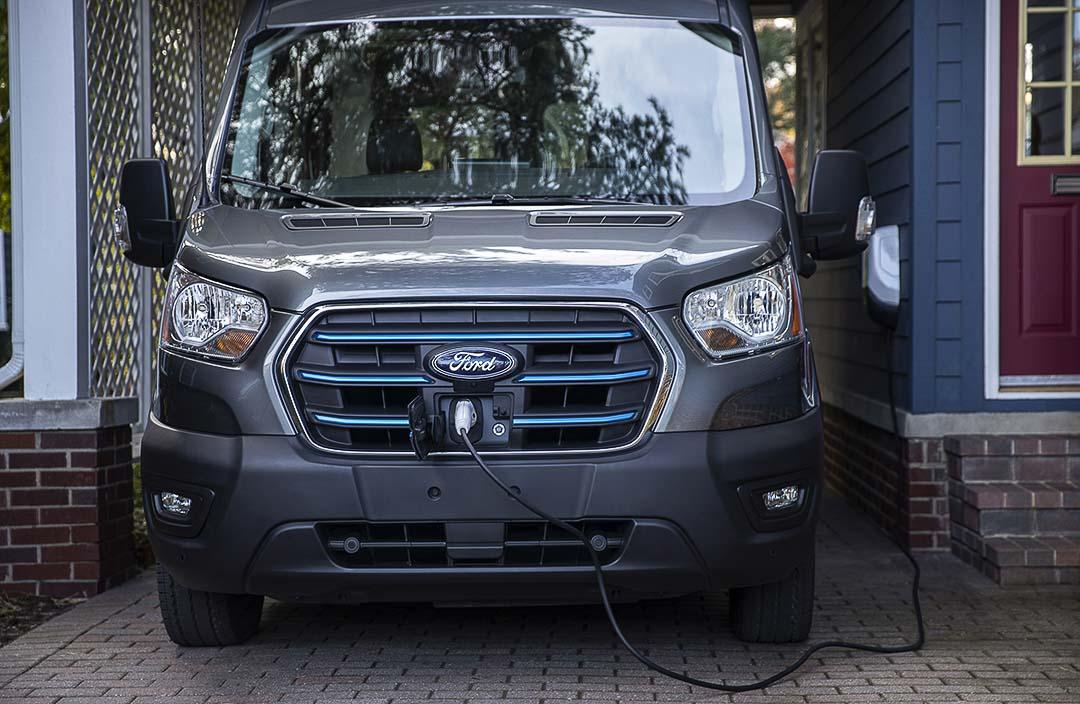 vue avant du Ford E-Transit 2022 branché à une borne électrique et stationné dans une entrée d'une maison