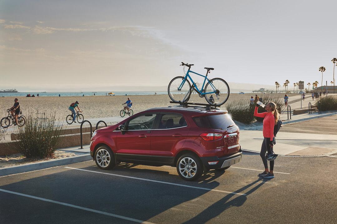 vue trois quart arrière du Ford EcoSport 2021 stationné proche de la plage avec un vélo sur son toit