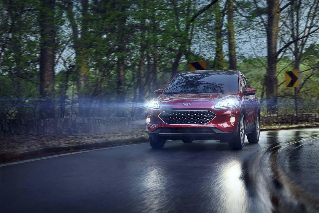 vue avant du Ford Escape hybride rechargeable 2021 roulant sur une route mouillée