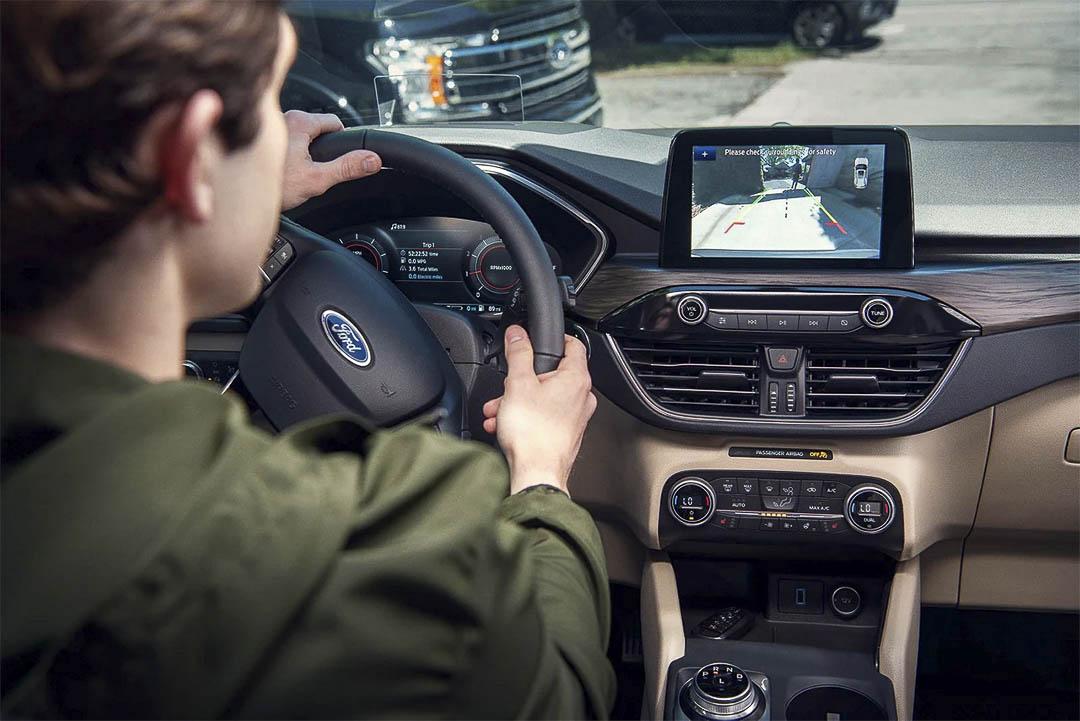 vue de la console central, de l'écran et du volant à l'intérieure du Ford Escape hybride rechargeable 2021