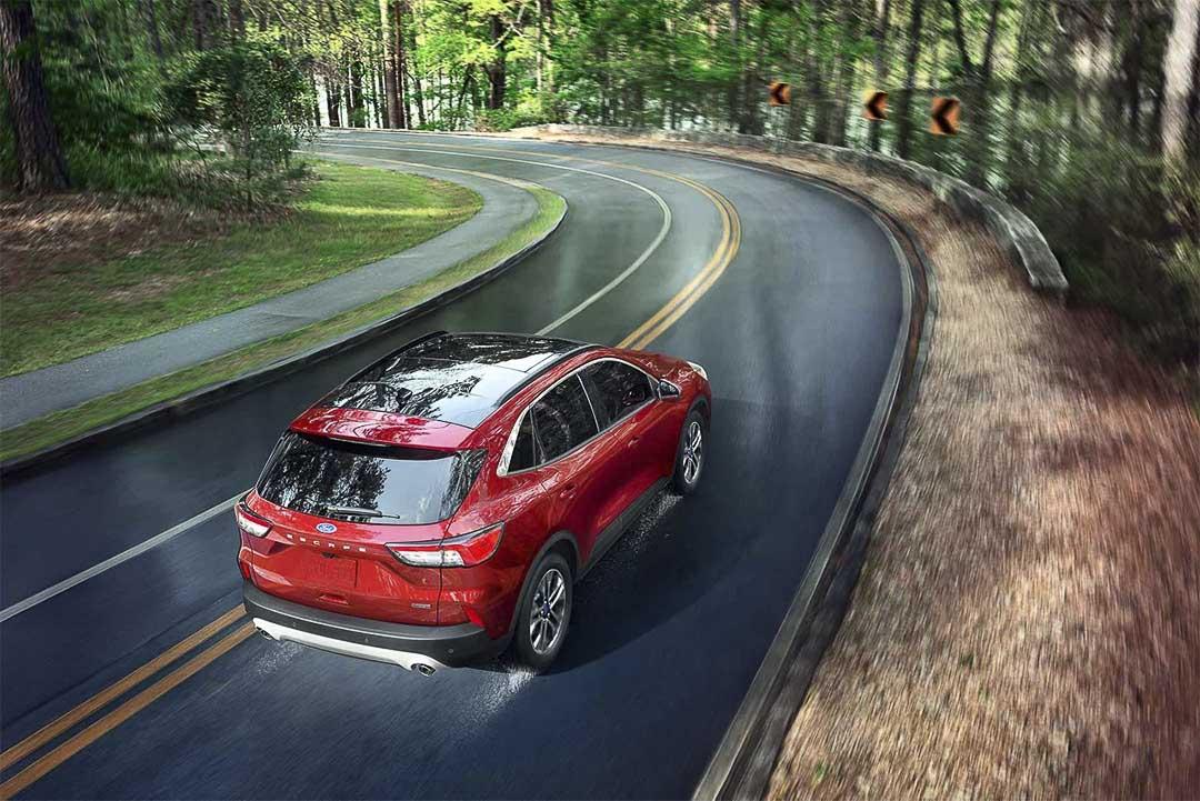 vue trois quart arrière du Ford Escape hybride rechargeable 2021 roulant sur une route